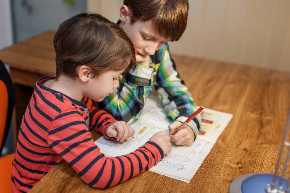 Little boys doing math homework at home, help
